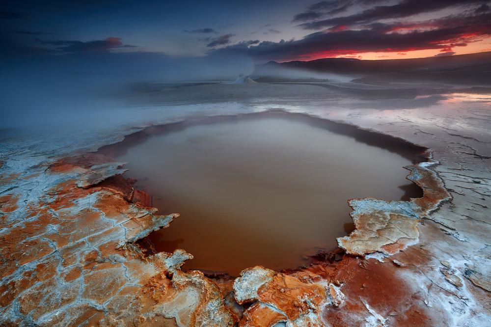 Steaming orange hot spring pool in the Iceland Highlands at dusk.