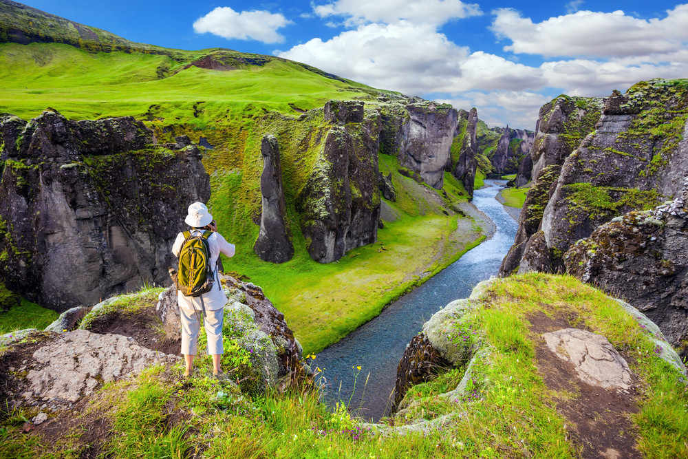 Person standing enjoying the view of a beautiful green river canton. Iceland in August