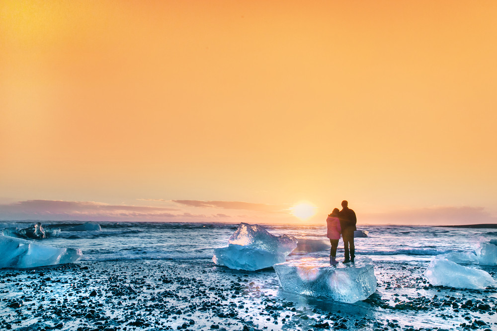 Couple stand on an ice block on the beach and look out across a sunset sky. Iceland honeymoon ideas.