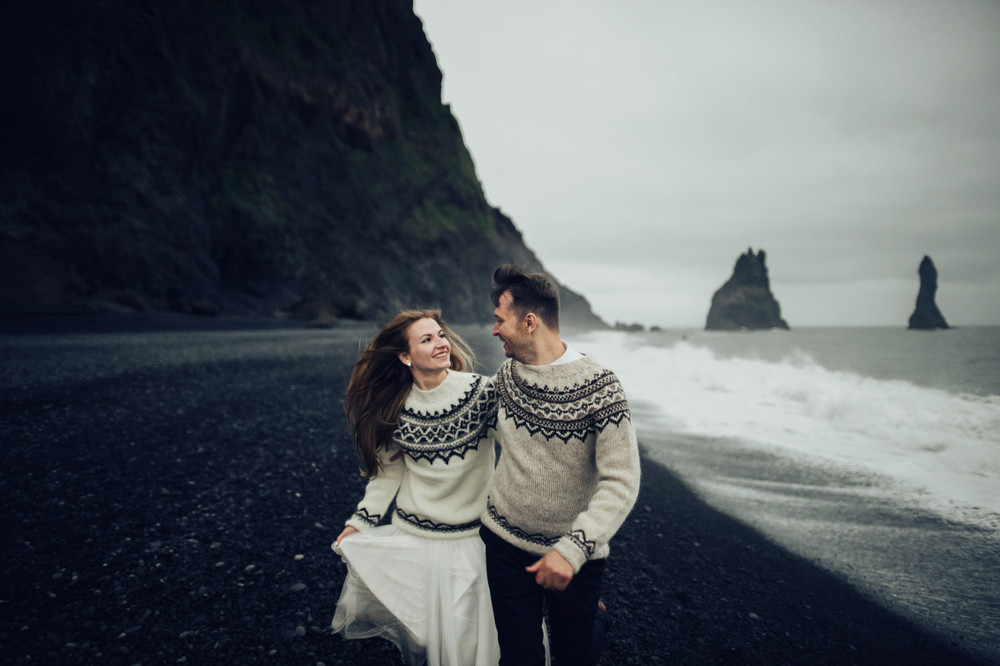 Young couple in Iceland sweaters on a black sand beach. Romantic places in Iceland.