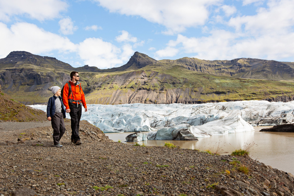 Father and son in hiking gear walking close to a glacier with blue skies and mountains in the distance. Family travel in Iceland.