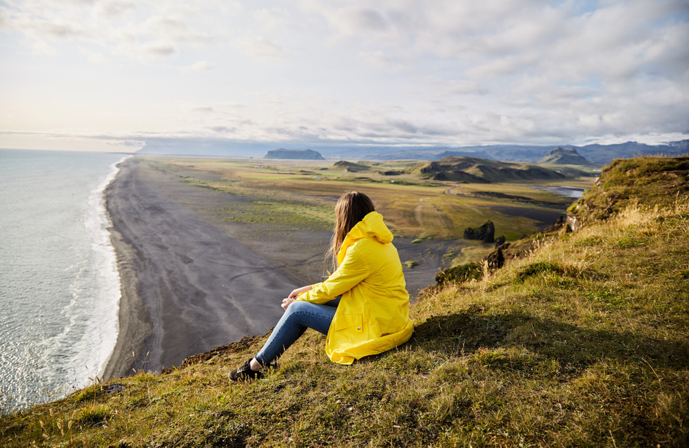 Girl in a yellow coat sitting and enjoying a view across a black sand beach. Nature is free. Iceland on a budget