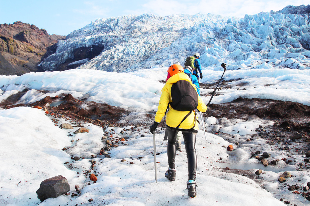 Two people with walking poles hiking across glacier surface. How expensive is Iceland.