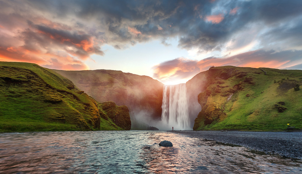 Distant view of Skogafoss waterfall at sunset. One of the biggest waterfalls in Iceland.