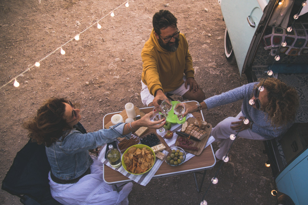Friends enjoying drinks and snacks at a table outside a camper van. Being a vegetarian in Iceland is easy.