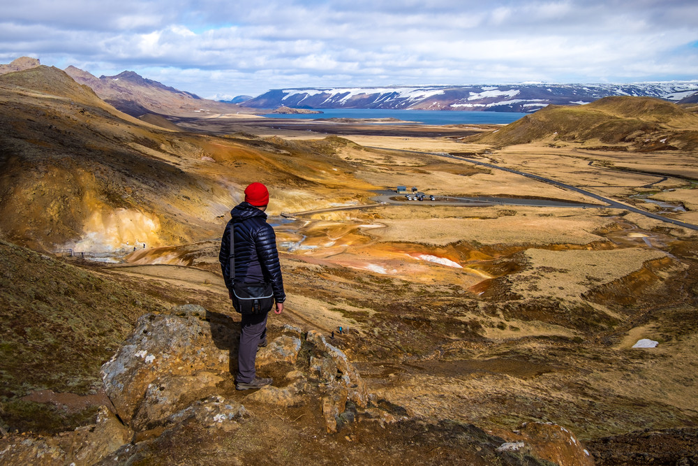 Man standing and looking out at orange landscape and lake in Iceland's Reykjanes Peninsula