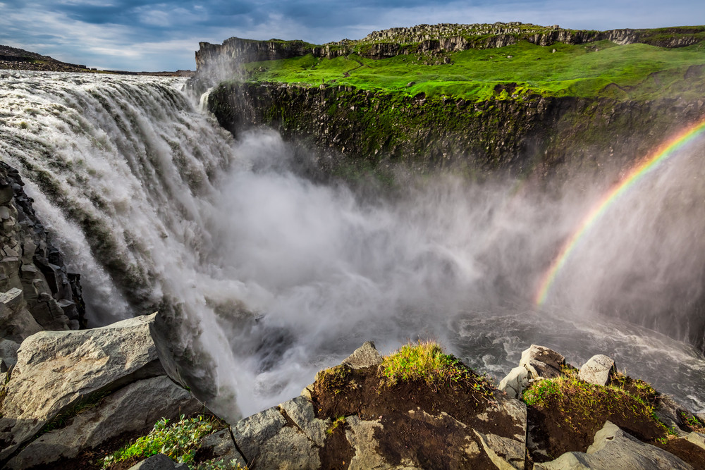 A river in full flow cascades down into a steep gulley where a rainbow rises up from the mists. Dettifoss, the most powerful waterfalls in Iceland