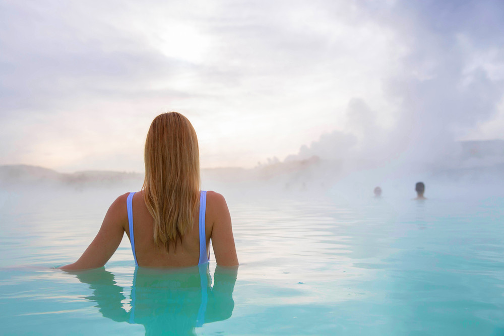 Woman standing in steamy pool. The Blue Lagoon Iceland.