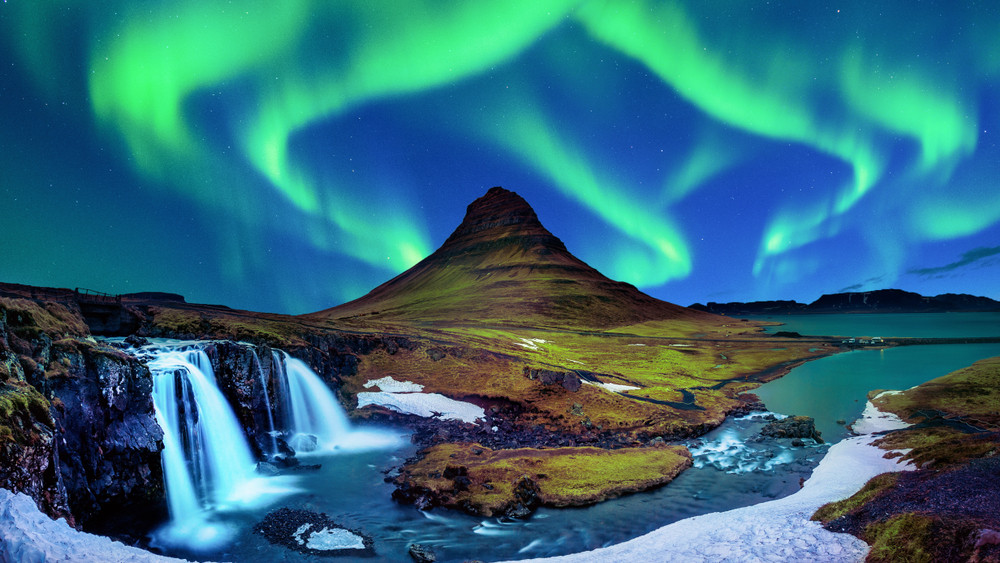 Iceland photography of green Northern Lights over a beautiful mountain and waterfall scene.