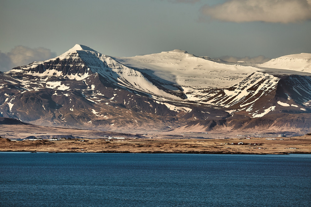 View across water to a snowy mountain peak. Mount Esja near Reykjavik is a popular place for hiking in Iceland.