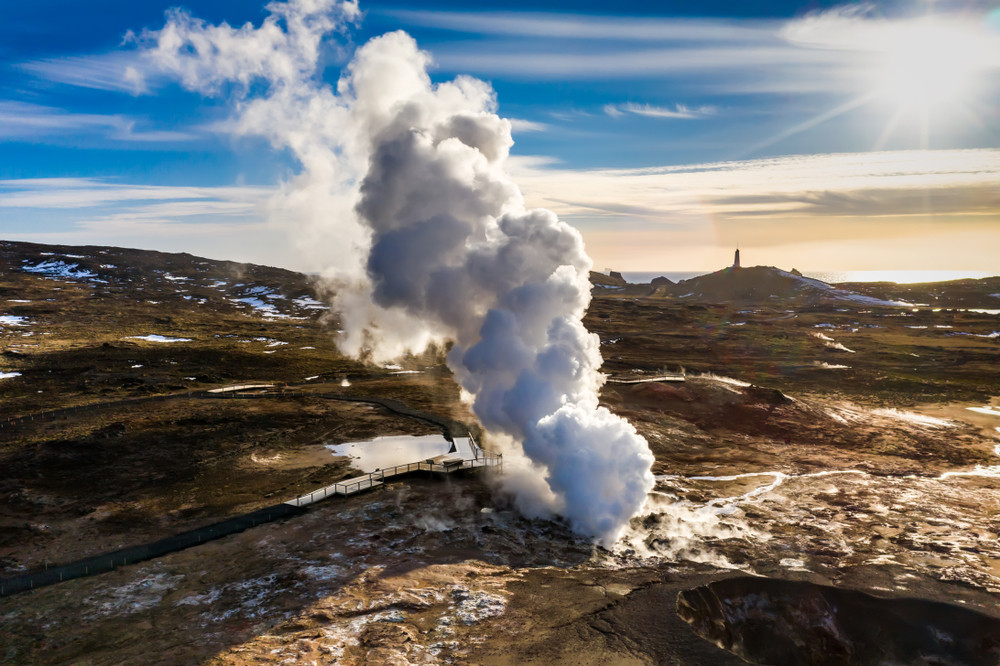 Aerial view of large steam cloud and raised walkways over geothermal zone at Iceland's Reykjanes Peninsula