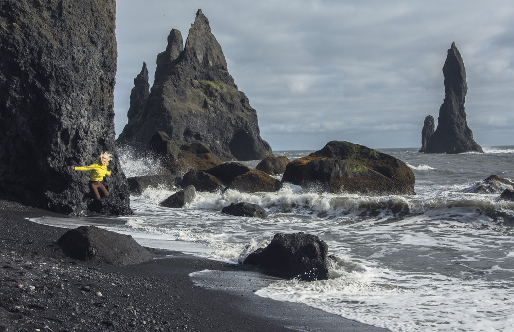Girl in yellow top jumps into the air on a black sand beach. Dark cliffs and rocky outcrops in the sea. Reynisfjara Black Sand Beach is on Iceland's South Coast.