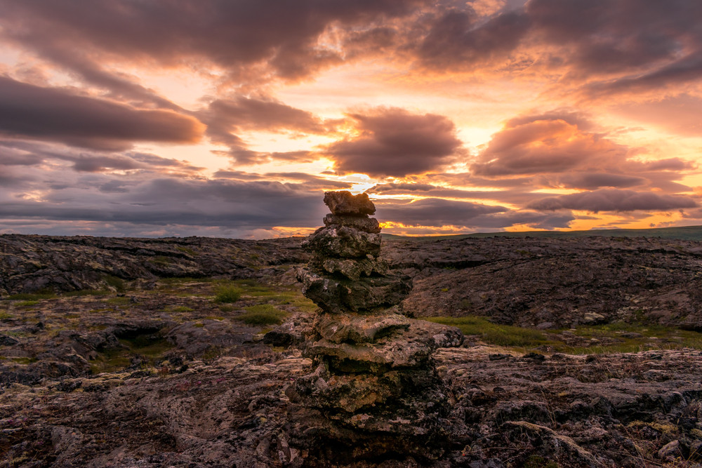 Stone cairns in Iceland under a sunset sky.