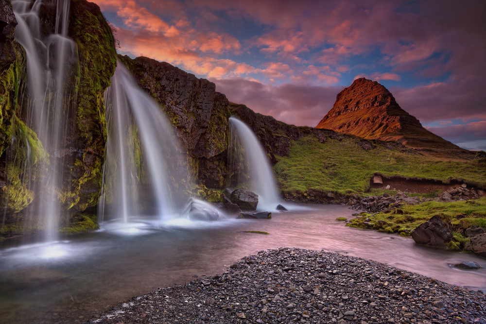 Pink sunset sky over a mountain and beautiful waterfall. On the Snæfellsnes Peninsula one of the top road trips in Iceland.