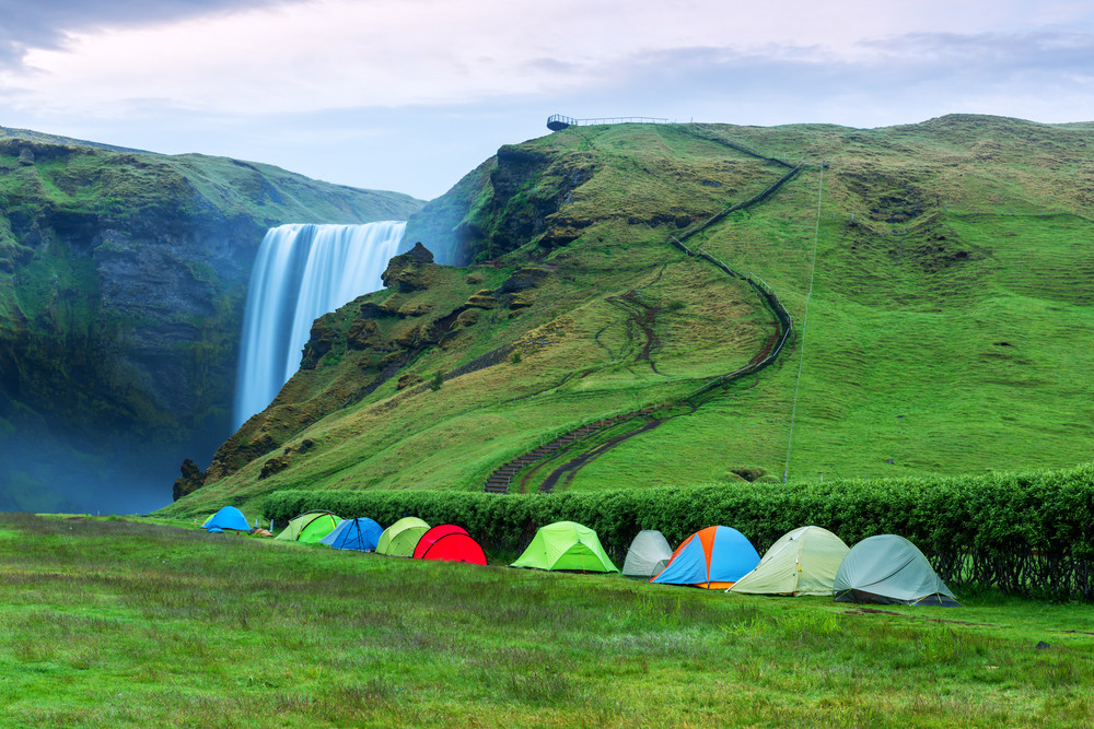 Coloured tents in a green landscape with a waterfall behind. Iceland camping law.