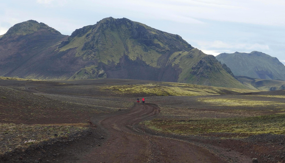 Dark volcanic landscape of mountains and a gravel road. Bicycles in distance cycling in Iceland.