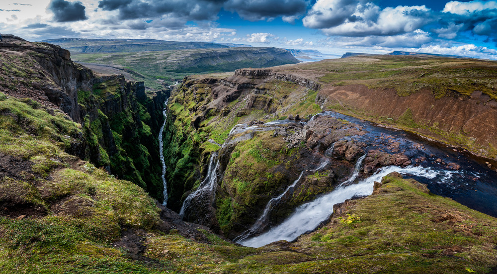 A wide landscape of highland country with several slim waterfalls plunging down into a gorge. The Glymur Waterfall is a great place for hiking in Iceland.