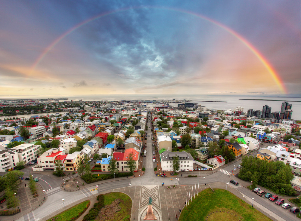 Colourful cityscape with a full rainbow arcing across the sky. Reykjavik is the venue for the Iceland Airwaves Festival
