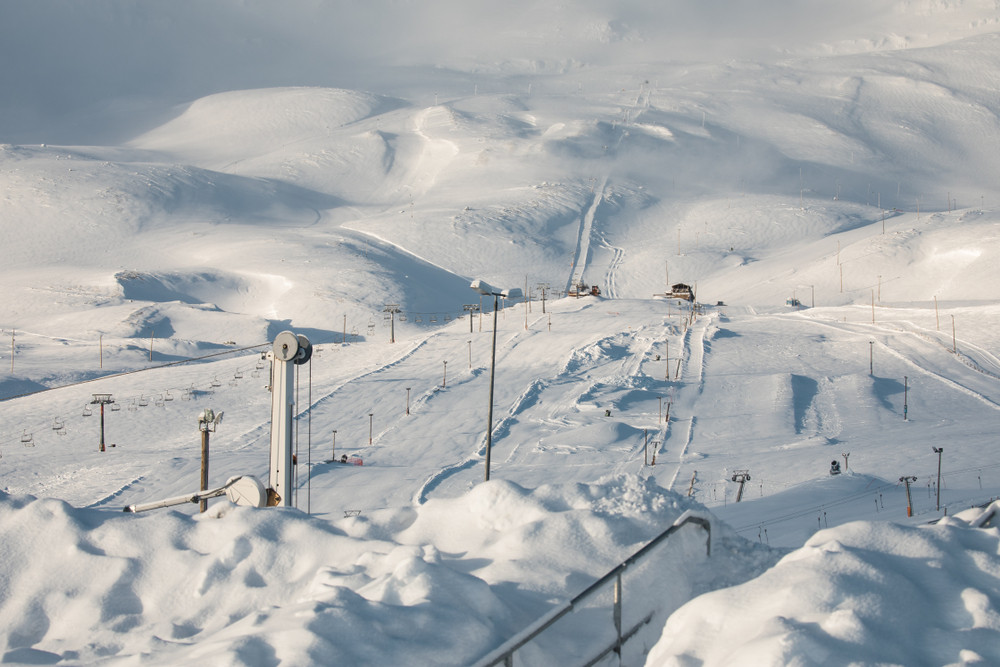 View across a quiet ski resort, groomed runs, ski lifts. Skiing in Iceland.