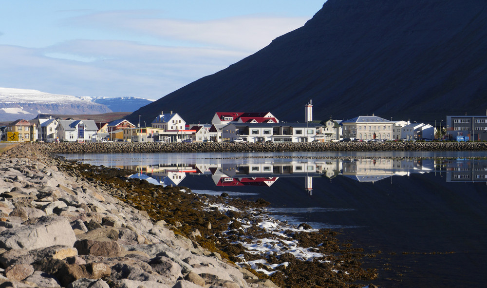 Coastal town in the Westfjords, Iceland. Houses reflected in water with snowy mountains behind.