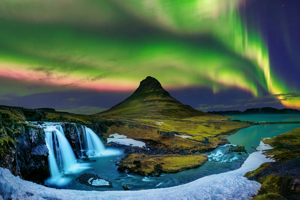 waterfalls, river and striking mountain view bathes under the green, yellow and pink of the northern lights in Iceland.