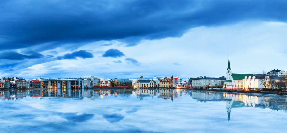 Cityscape of Reykjavik with blue skies reflected in the sea. Explore with the Reykjavik city card.