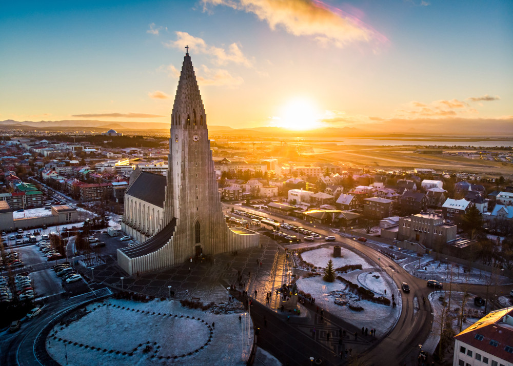 City scape at sunset with orange and blue sky. Striking church spire rising up much taller than surrounding buildings. The Architecture of Iceland.