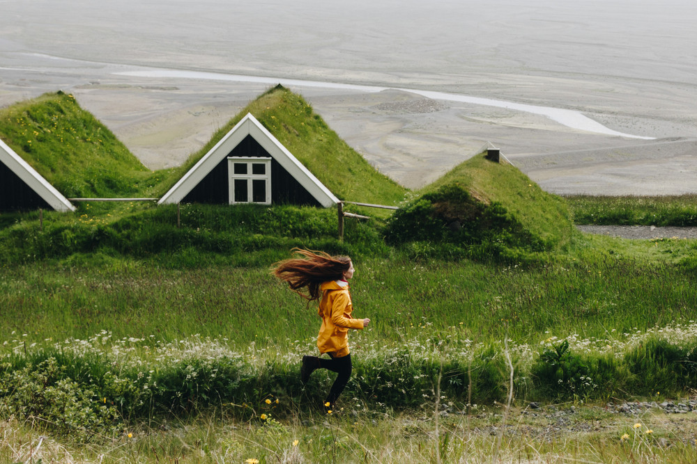 girl in yellow coat runs past turf roof houses near ocean. Iceland national flag and identity