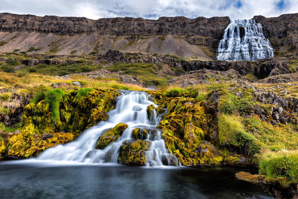 Dynjandi Waterfall in the Westfjords, Iceland. Cascading dovetail falls in a rocky and mossy landscape.