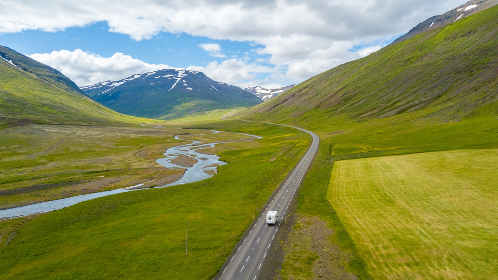 A beautiful green valley with a road running through it. How to find the best camper rental in Iceland.