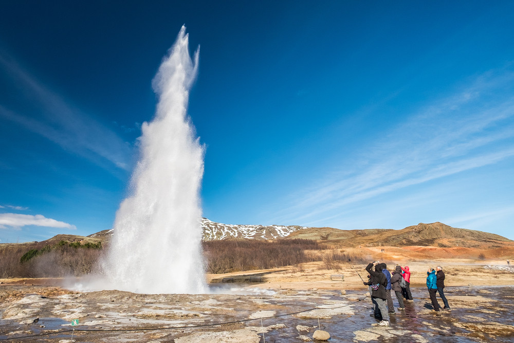 Small group of people standing next to erupting geyser. Fewer people visit Iceland in Spring.