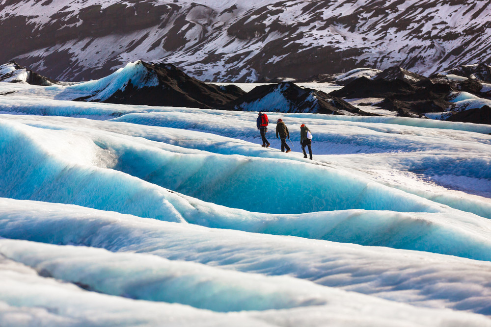 Three walkers on a ridged glacier glowing blue. Camping and caravanning in Iceland in winter.