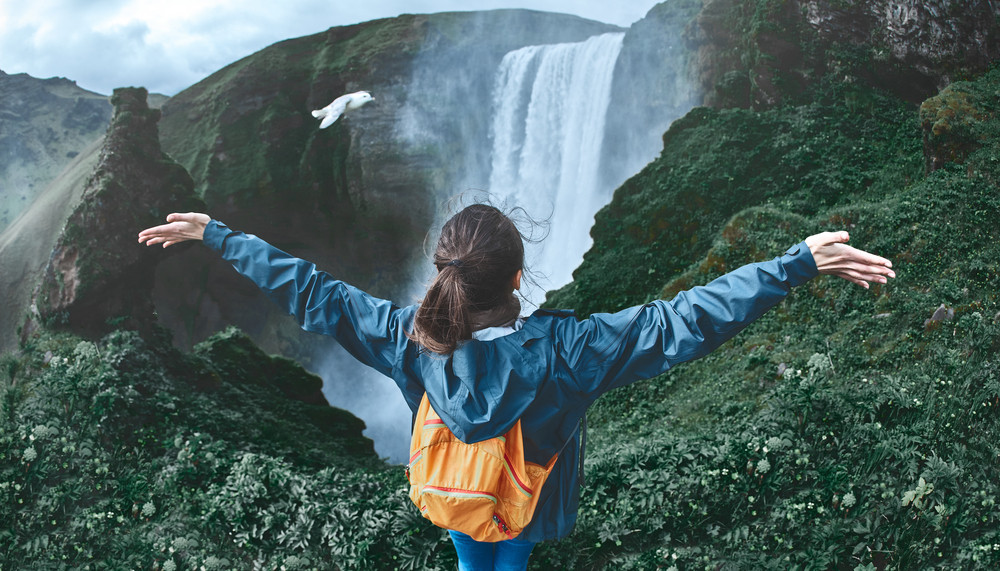 Woman with outstretched arms in front of a waterfall. Just how expensive is Iceland?