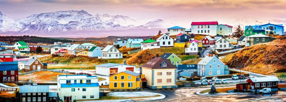 Colourful painted houses with background of lake and mountains. Architecture of Iceland