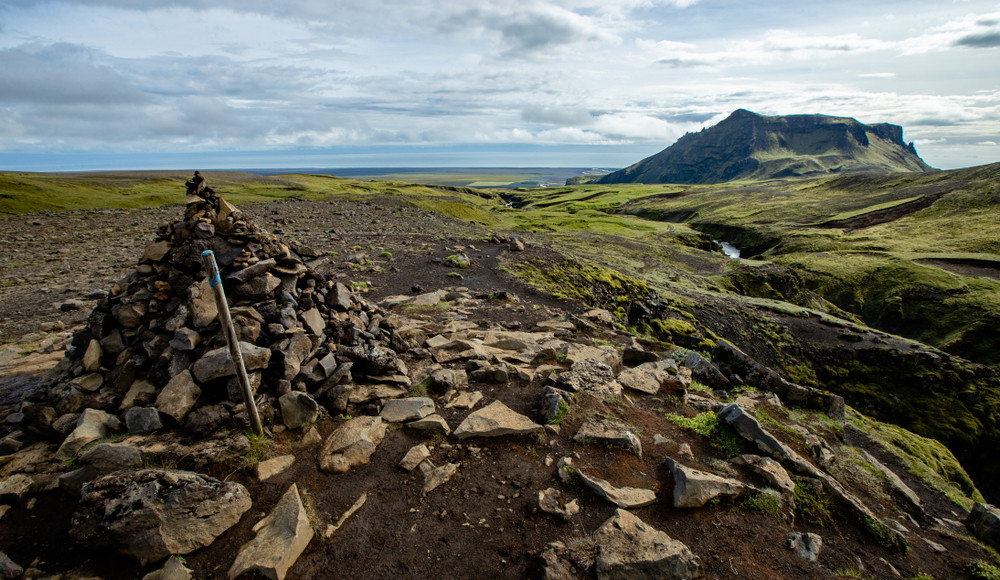 Stone cairns in Iceland showing the hiking path in an open landscape.