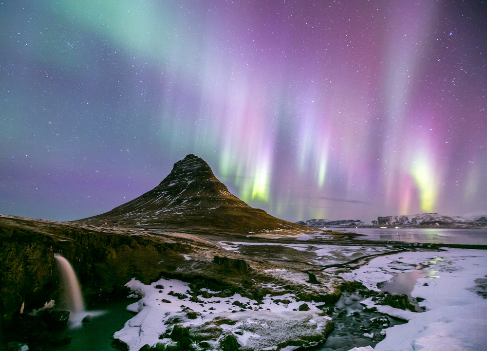 Small mountain at night with snowy landscape and pink and green northern lights - Iceland in spring