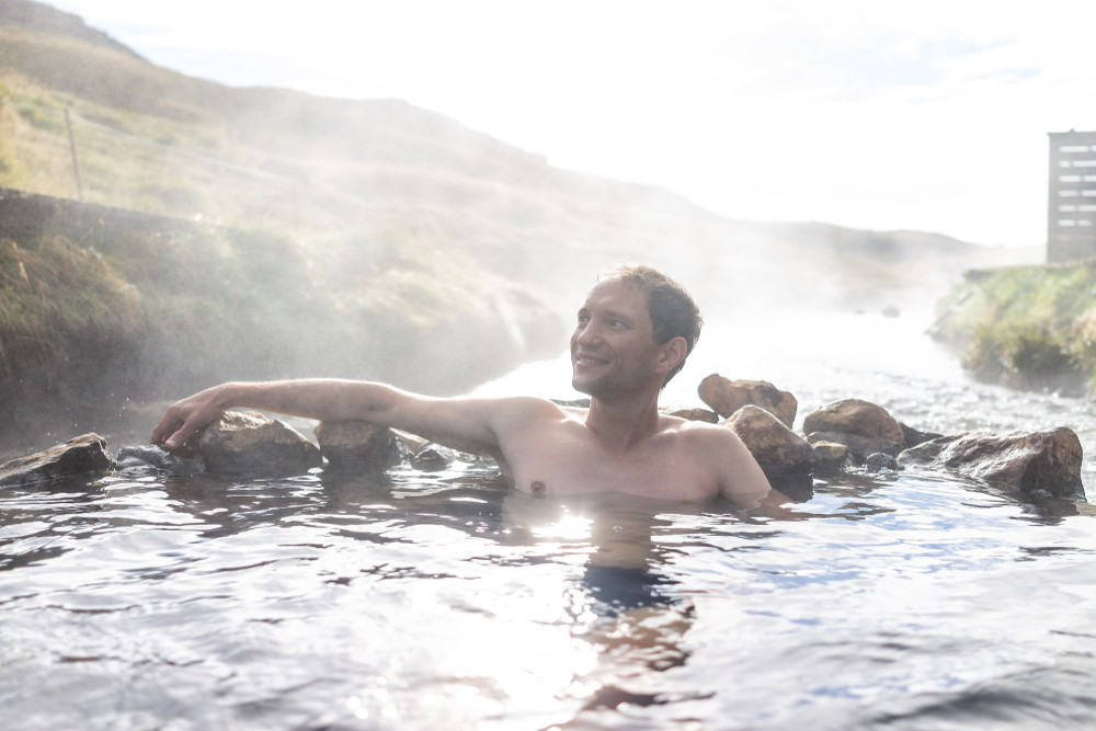 Young man bathing in a hot spring river pool. Hiking in Iceland.