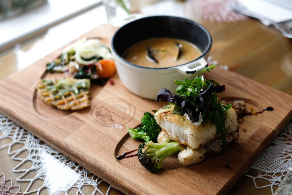 Wooden platter of delicious food, fish, salad and seafood soup. What food should I try in Iceland?