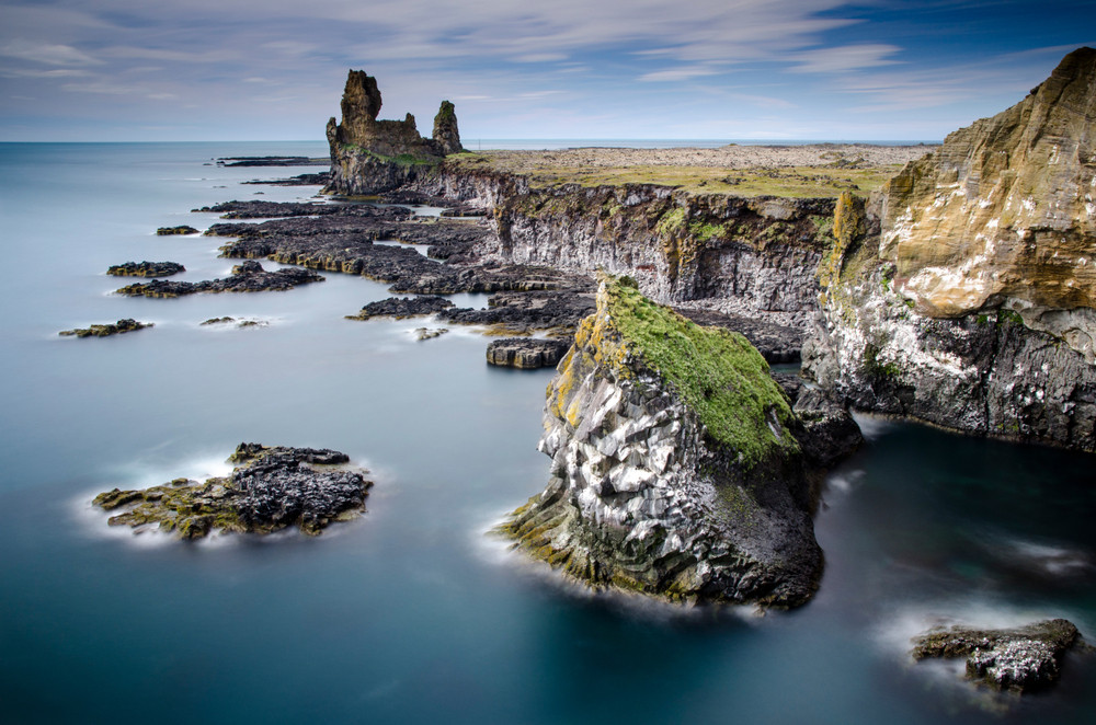 Dramatic coastline view of dark craggy cliffs and columns and a calm sea. Snaefellsnes Peninsula, Iceland.