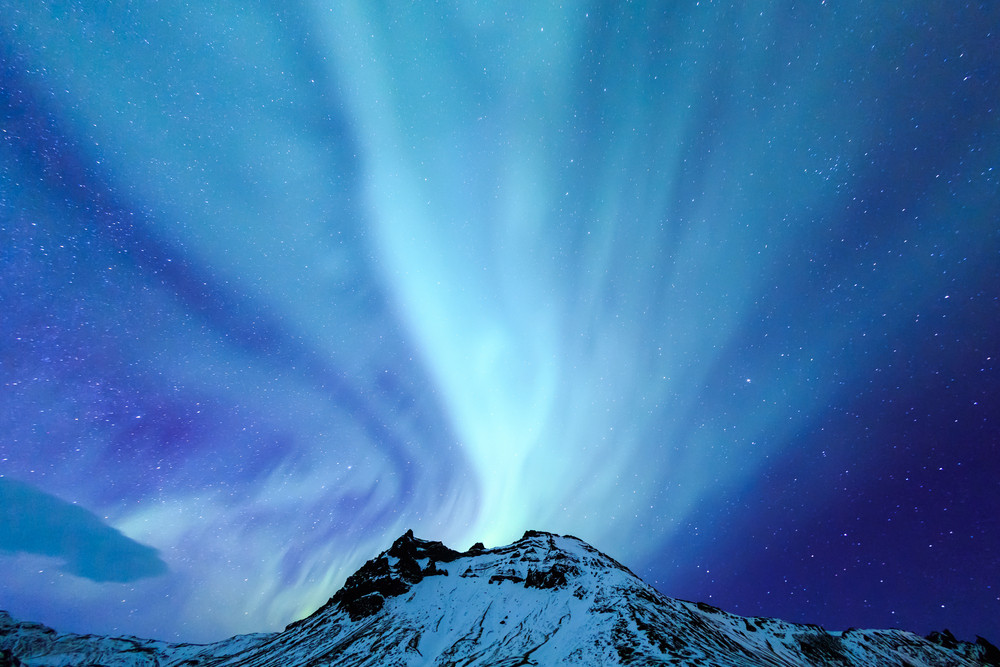 Starry night sky over mountain top with bright blue northern lights above. Does Iceland get Polar Nights?