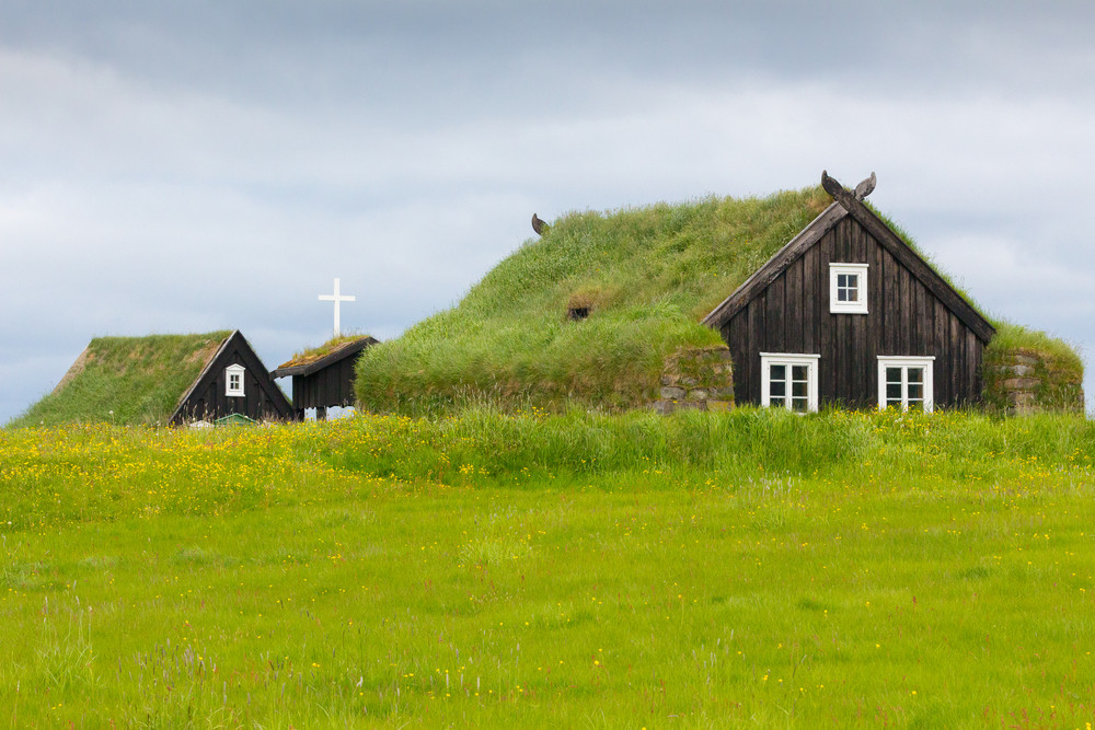 Turf roofed wooden house in a green meadow. This Open Air  museum near Reykjavik is one of the most interesting 19th Century historical museums in Iceland.