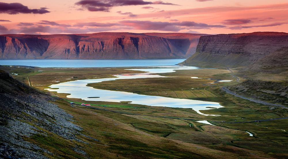 Driving in the Westfjords is grand and beautiful. Remote landscape of water and cliffs with pink sky.