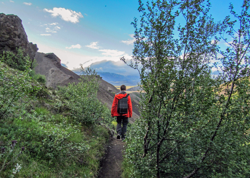 Man in red jacket walking a mountain path. Right to roam Iceland.