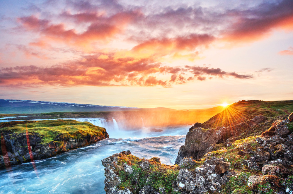 Sunset over a beautiful waterfall. Low sun and rosy sky. Iceland photography is too easy.