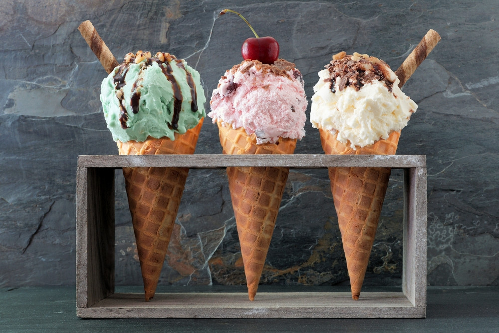 Icelandic ice cream - three cones in a stand with sauce, wafers and a cherry on top