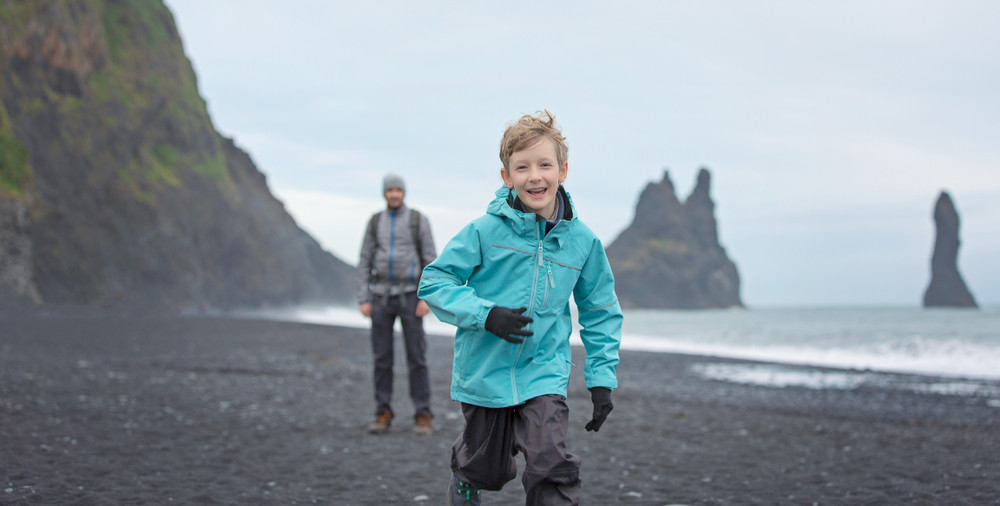 Young boy in warm clothes running and smiling across a black sand beach. Family travel in Iceland.