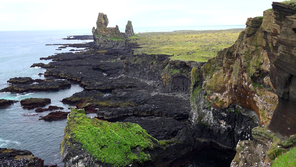 Black, craggy volcanic coastline with pillars of rock and green-topped cliffs. Self-drive road trips in Iceland.