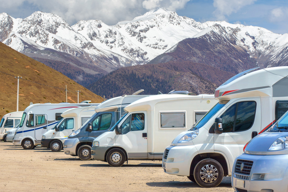 Row of parked motorhomes and camper vans with mountain background. Camping Golden Circle, Iceland.