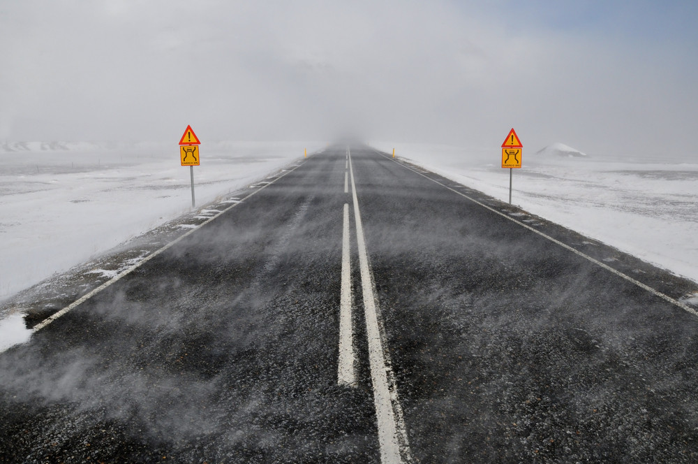A road leads off and disappears into cloud. Wintry weather with snow and low visibility. Iceland mobile network and coverage is useful in a storm!