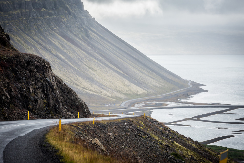 Long empty road stretching between steep mountain and sea. Driving in the Westfjords.